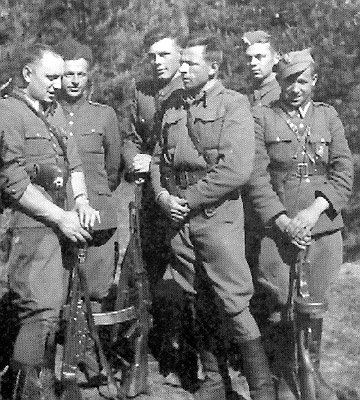 """Podlasie, prawdopodobnie 1950, żołnierze zoddziału kpt. Kazimierza Kamieńskiego """"Huzara"""". Stoją odlewej: sierż. Lucjan Niemyjski """"Krakus"""", 22 sierpnia 1952 otoczony przez GrOp UB-KBW popełnił samobójstwo; Józef Brzozowski """"Zbir"""", """"Hanka"""", zginął latem 1952 wwalce zKBW; Wacław Zalewski """"Zbyszek"""", zamordowany 11 października 1953 wwięzieniu wBiałymstoku; ppor. Witold Buczak """"Ponury"""", zginął wwalce zKBW 28 maja 1952; NN """"Jurek""""; Eugeniusz Welfel """"Orzełek"""", zginął wwalce zKBW 30 września 1950 (fot.podziemiezbrojne.blox.pl)"""