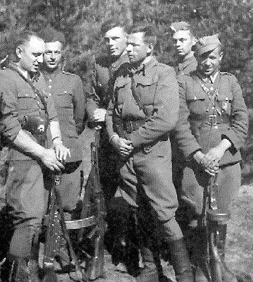 """Podlasie, prawdopodobnie 1950, żołnierze zoddziału kpt. Kazimierza Kamieńskiego """"Huzara"""". Stoją od lewej: sierż. Lucjan Niemyjski """"Krakus"""", 22 sierpnia 1952 otoczony przezGrOp UB-KBW popełnił samobójstwo; Józef Brzozowski """"Zbir"""", """"Hanka"""", zginął latem 1952 wwalce zKBW; Wacław Zalewski """"Zbyszek"""", zamordowany 11 października 1953 wwięzieniu wBiałymstoku; ppor. Witold Buczak """"Ponury"""", zginął wwalce zKBW 28 maja 1952; NN """"Jurek""""; Eugeniusz Welfel """"Orzełek"""", zginął wwalce zKBW 30 września 1950 (fot. podziemiezbrojne.blox.pl)"""