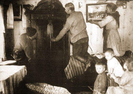 """Aktywiści wiejscy wynoszą dobytek """"rozkułaczanego"""" chłopa naPodolu w1929 r."""