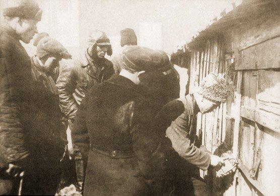 Aktywiści wiejscy przeszukujący zabudowania wposzukiwaniu zboża w1933 r.
