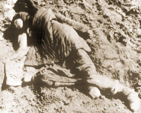 Ciało zmarłej z głodu kobiety na ziemi, na której nie rośnie już nawet trawa