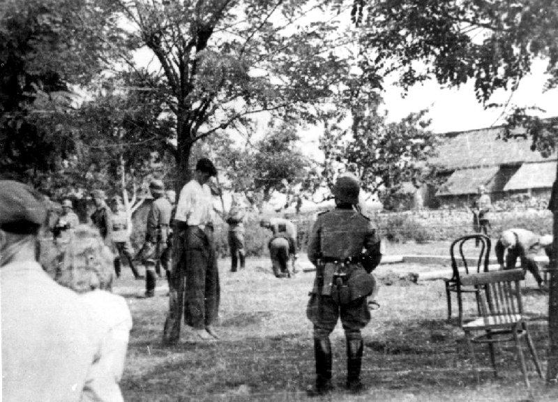 Po pierwszej egzekucji w Dmeninie, pow. radomszczański. W tle widoczne stawianie szubienicy, b.d. [ze zbiorów IPN].