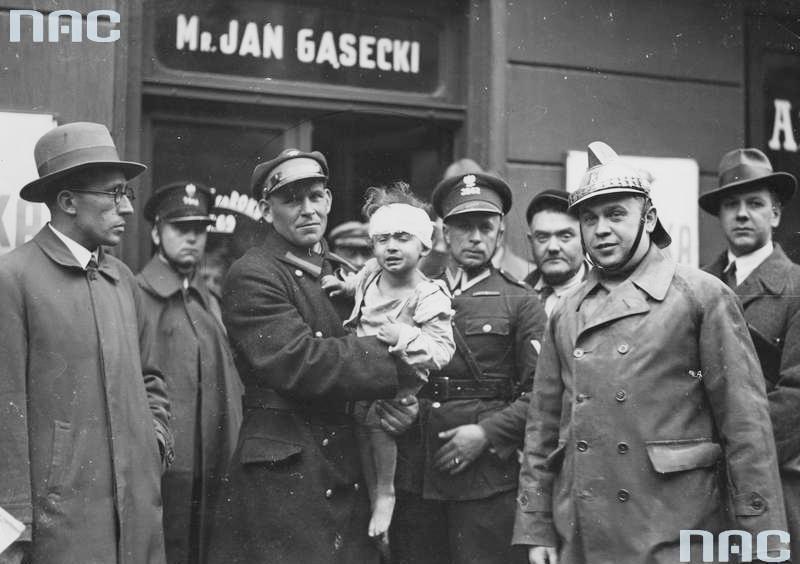 Katastrofa budowlana w kamienicy przy ul. Freta 16w Warszawie (31 maja 1935 r.). Policjanci i strażak (z prawej) z uratowanym spod gruzów dzieckiem.