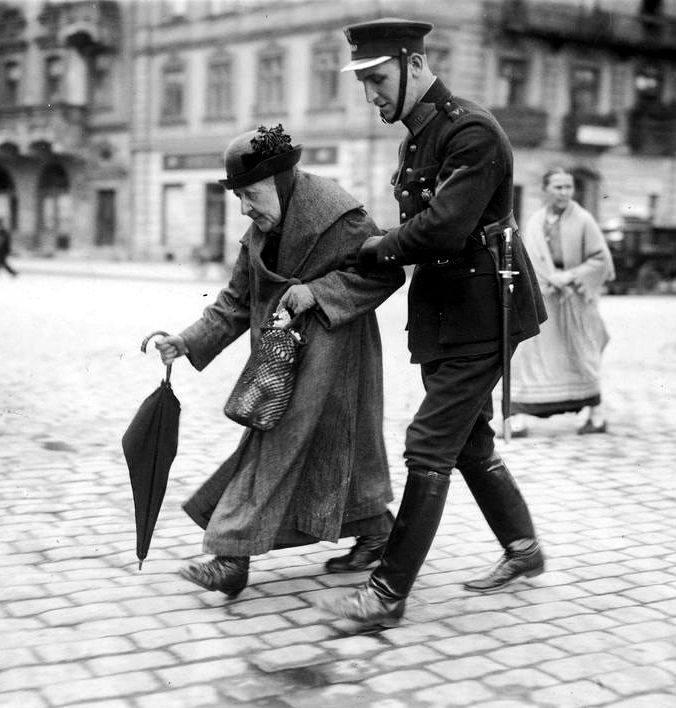 Policjant przeprowadzający staruszkę przez ulicę Krakowskie Przemieście przechodzące w plac Zamkowy - w głębi ulica Podwale i zabudowa północnej pierzei tej ulicy z charakterystyczną kamienicą Dziewulskich (lipiec 1925 r.).