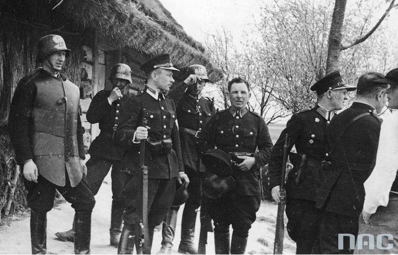 Funkcjonariusze policji przed wejściem do kryjówki bandy Maczugi. Z lewej widoczny policjant w kuloodpornej zbroi płytowej i hełmie, który miał wejść pierwszy do domu bandytów (1934 r.).