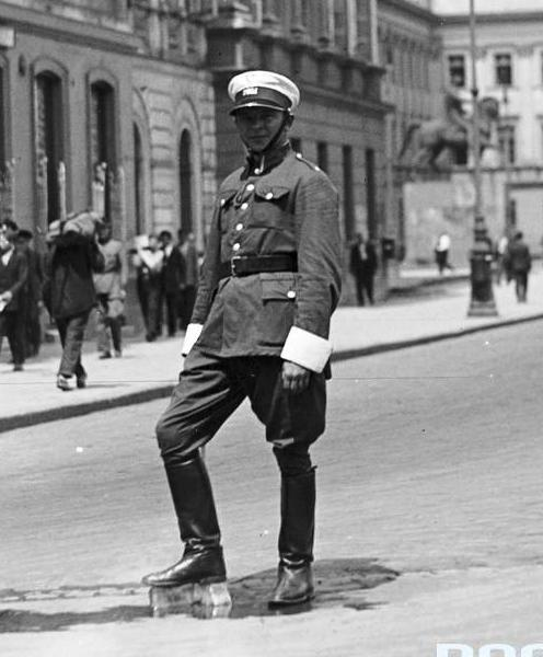 Policjant kierujący ruchem na placu Marszałka Józefa Piłsudskiego w Warszawie chłodzi nogi od upału stawiając je na bloku lodowym. W głębi widoczny pomnik księcia Józefa Poniatowskiego (lipiec 1932 r.).