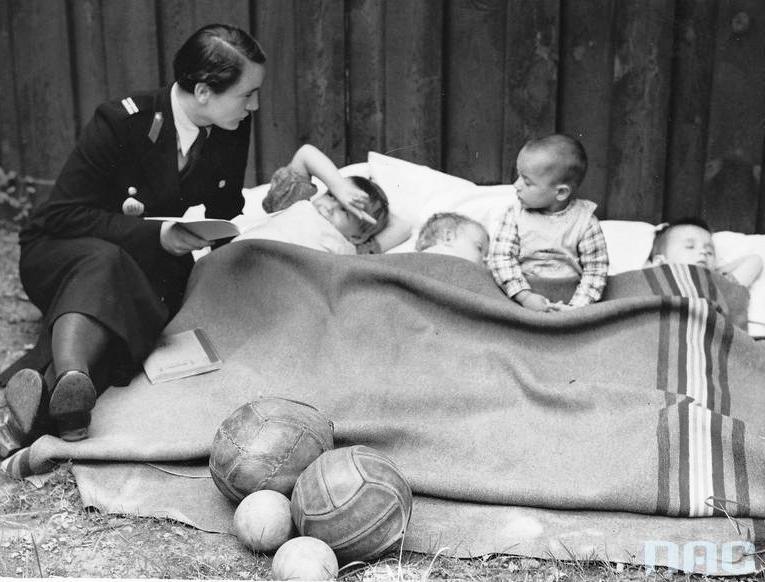 Referat policji kobiecej Centralnej Służby Śledczej w Łodzi. Policjantka czyta dzieciom przebywającym w Izbie Dziecka (1937 r.).