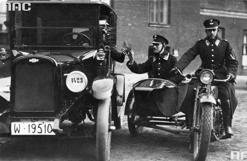 Funkcjonariusze policyjnego patrolu drogowego na motocyklu sprawdzają dokumenty kierowcy (przełom lat 20-tych i 30-tych).