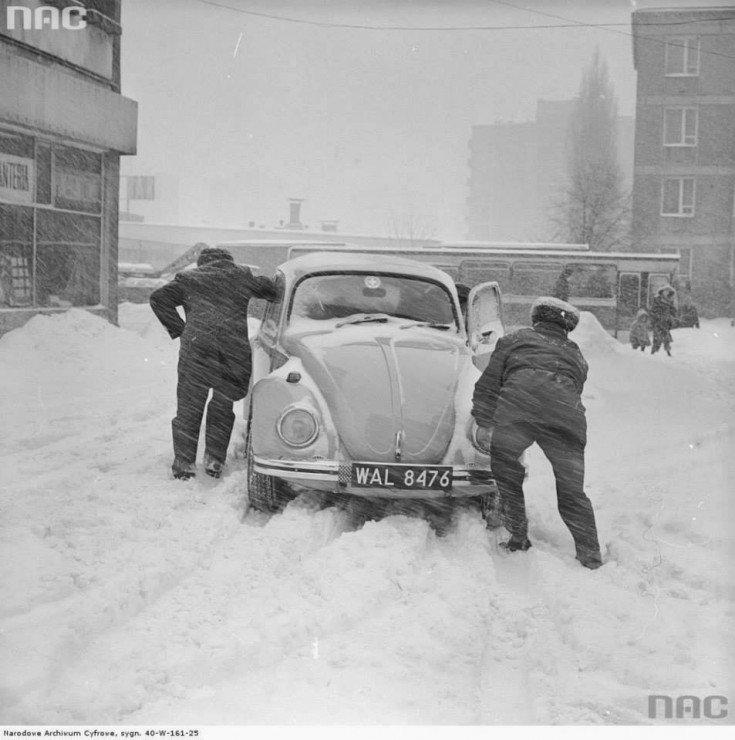 Mężczyźni pchają samochód Volkswagen Garbus nawarszawskim parkingu podczas Zimy Stulecia