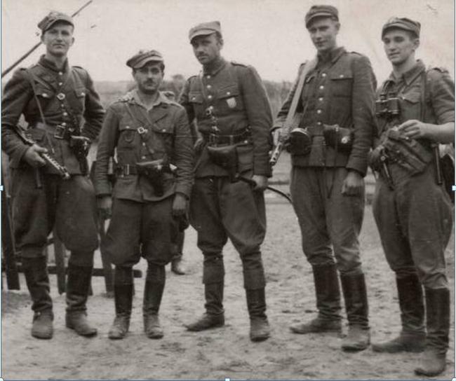 """Kadra 5 Wileńskiej Brygady AK. Od lewej: ppor. cz. w. Henryk Wieliczko """"Lufa"""" (zamordowany 14 III 1949 r. na Zamku Lubelskim, miał 27 lat), por. Marian Pluciński """"Mścisław"""" (zamordowany 28 VI 1946r. w więzieniu w Białymstoku, miał 34 lata), mjr Zygmunt Szendzielarz """"Łupaszko"""" (zamordowany 8 II 1951 r. w więzieniu na Rakowieckiej w Warszawie, miał 41 lat), plut. Jerzy Lejkowski """"Szpagat"""" (ciężko ranny w walce w 1946 r., prześladowany przez aparat bezpieczeństwa, zmarł w 1992r.,) ppor. cz. w. Zdzisław Badocha """"Żelazny"""", (poległ w walce z UB w Czerninie koło Sztumu 28 VI 1946r., miał 23 lata) Zwraca uwagę staranne umundurowanie i świetne uzbrojenie partyzantów. Na kaburach pistoletów przypięte odznaczenia sowieckie – trofea z walk z bolszewikami. Szpicruta w reku majora znamionuje jego przywiązanie do tradycji kawaleryjskich. Białostocczyzna 1945 r."""