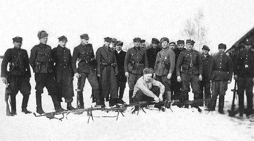 """Styczeń 1946 r. Część oddziału por. Leona Taraszkiewicza Jastrzębia"""". Dowódca siedzi przy RKM-ie; czwarty od lewej: Ryszard Jakubowski ps. """"Kruk""""."""