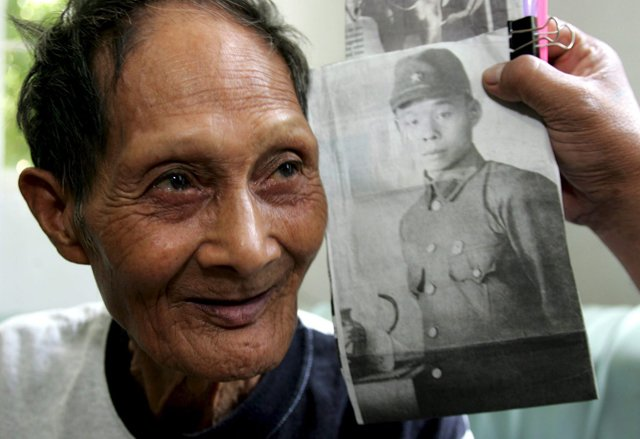 A FILIPINO HOLDS A PICTURE OF JAPANESE WW II SOLDIER