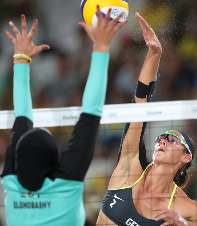 Germany's Kira Walkenhorst, right, tries to spike a ball past Egypt's Doaa Elghobashy, left, during a women's beach volleyball match at the 2016 Summer Olympics in Rio de Janeiro, Brazil, Sunday, Aug. 7, 2016. (AP Photo/Petr David Josek)