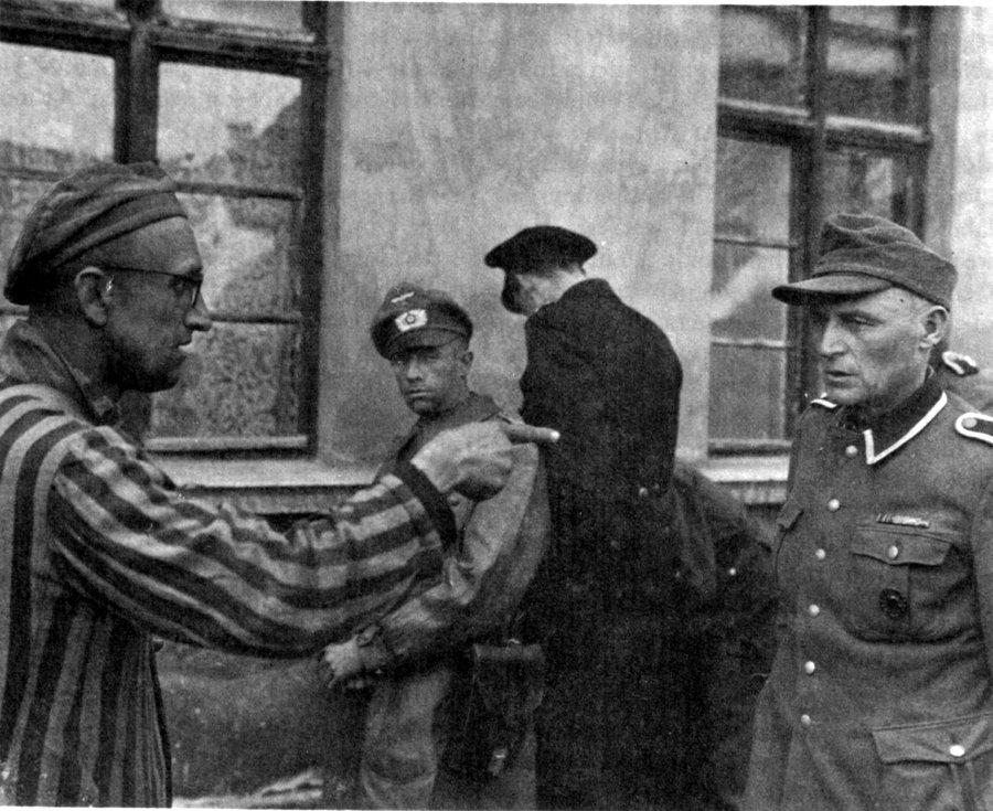 Ocalony więzień Buchenwaldu wytyka palcem strażnika z niemieckiej formacji SS, który znęcał się nad ludźmi w obozie, fot. wikipedia
