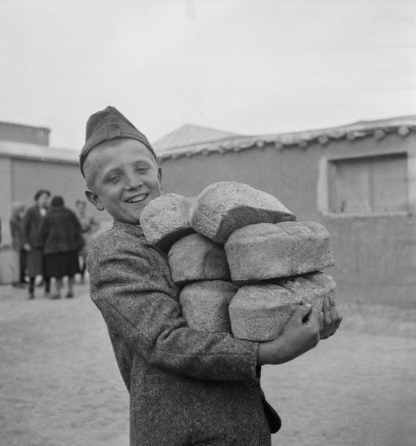chłopiec niosący bochenki chleba