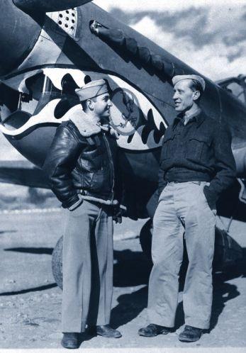 """Płk pil. Witold Urbanowicz (po prawej), legendarny dowódca 303. Dywizjonu podczas Bitwy oAnglię w1940 r., podczas służby wamerykańskiej 23. Grupie Myśliwskiej (tzw. """"Latających Tygrysów"""") wChinach w1943 r. Wtle samolot myśliwski typu Curtiss P-40 zcharakterystycznymi """"szczękami""""."""